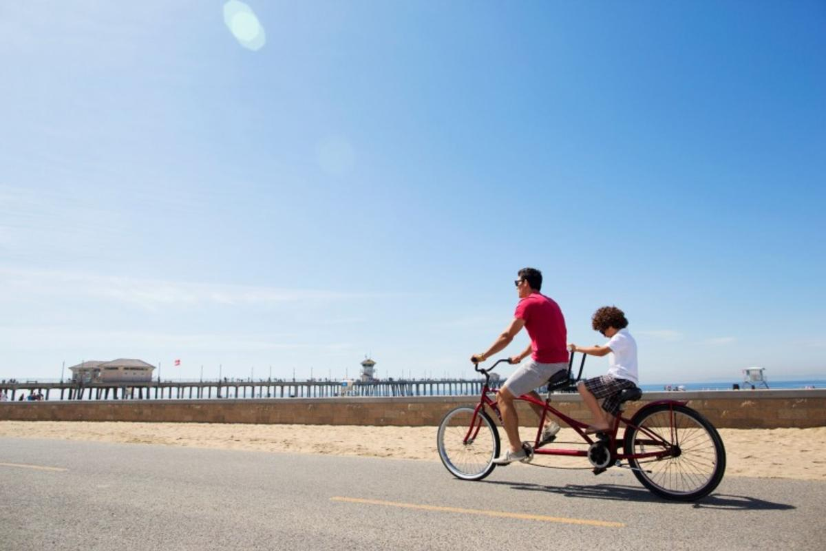 Father and son riding tandem bike on beach in Huntington Beach