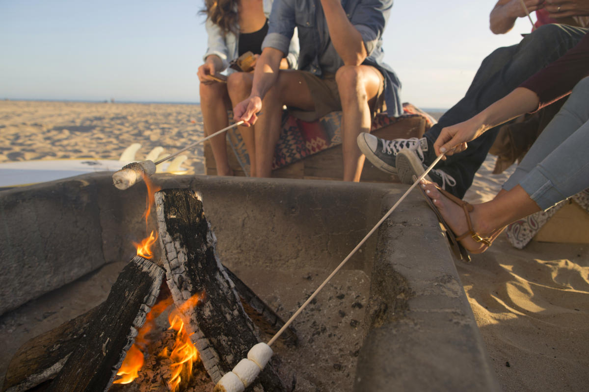 Friends roasting marshmallows on a beach bonfire in Huntington Beach