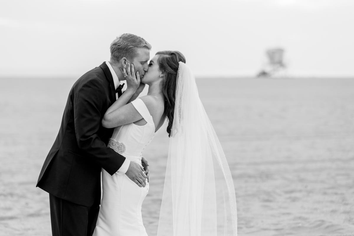 Newlyweds kissing on the beach in Huntington Beach