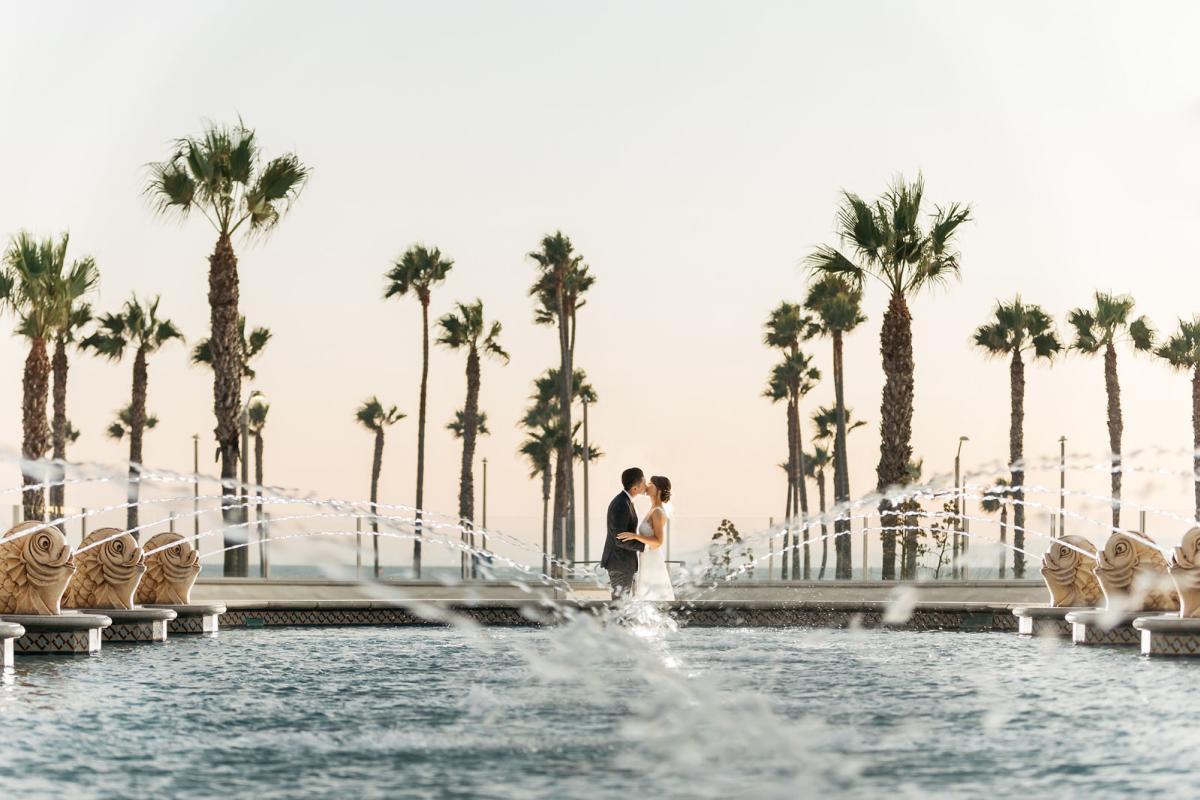 Newlyweds kissing at the Hyatt Regency Resort & Spa wedding venue in Huntington Beach