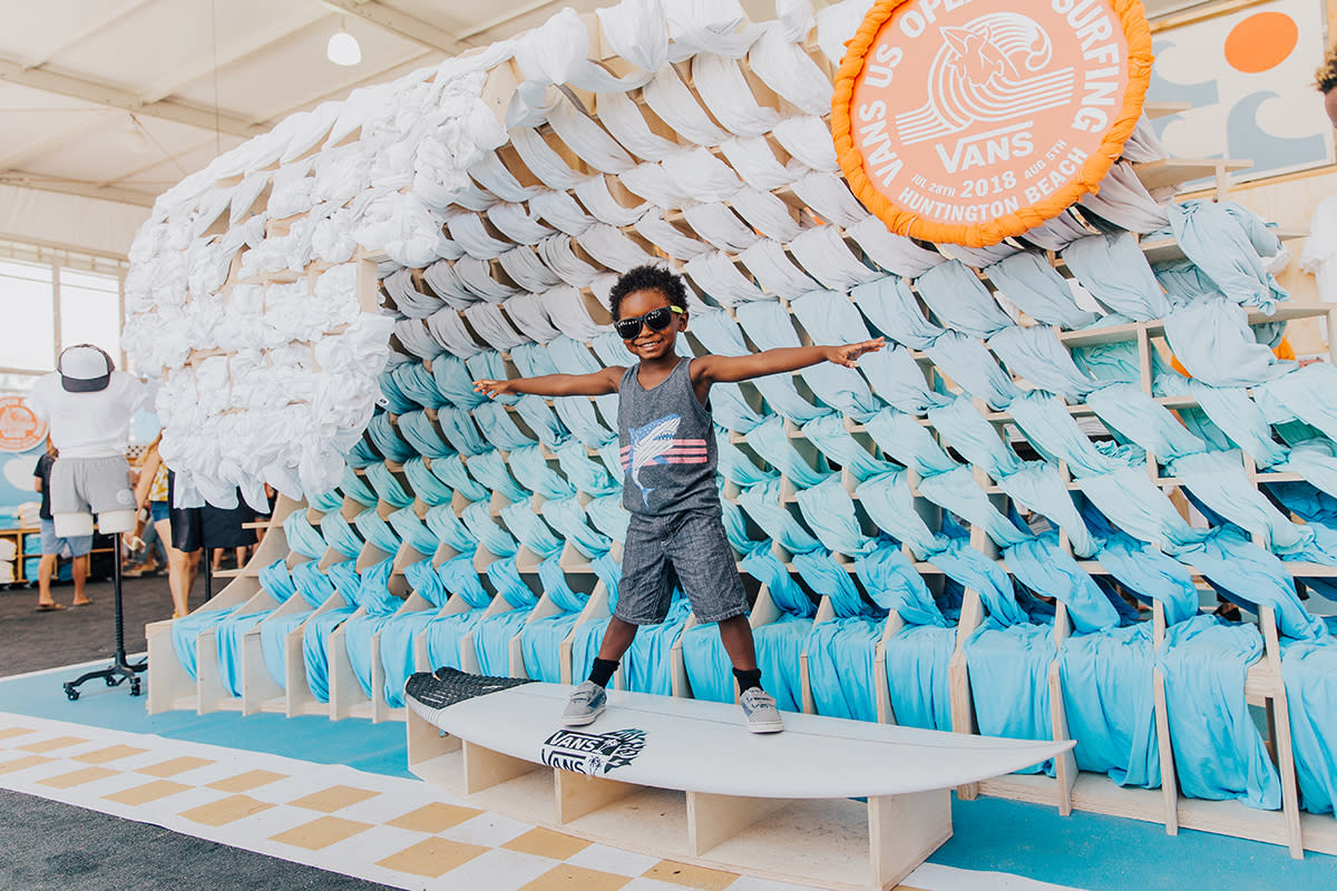 Young child posing on a surfboard at a display set up by Vans at the US Open of Surfing in Huntington Beach