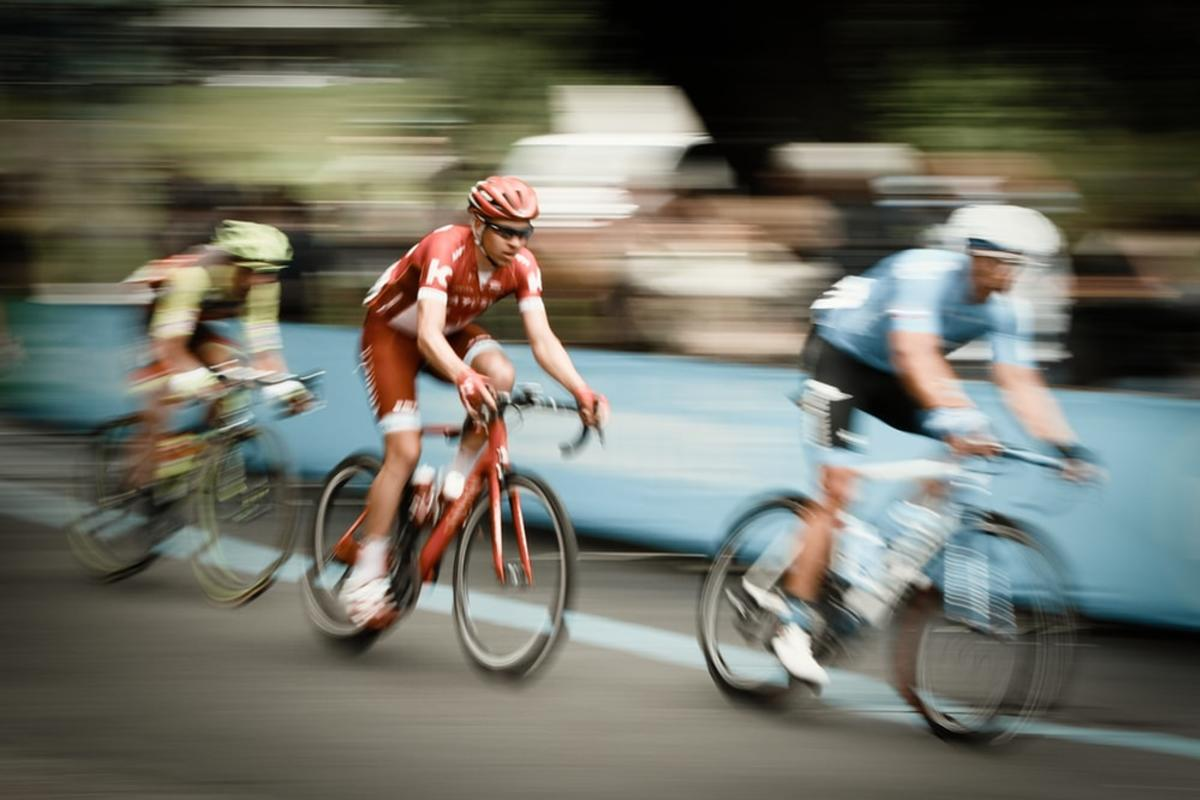time lapse photography of three men riding bicycles on road