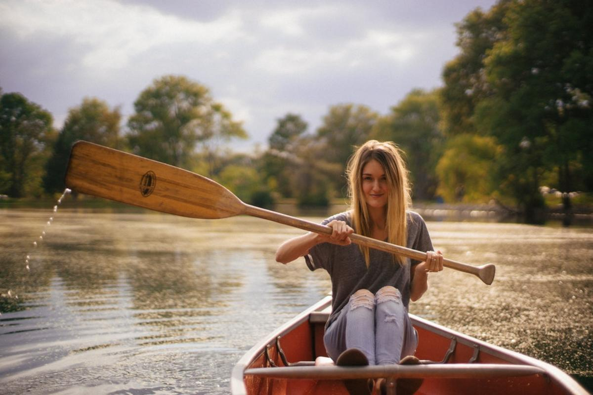 woman sitting in brown paddle boat