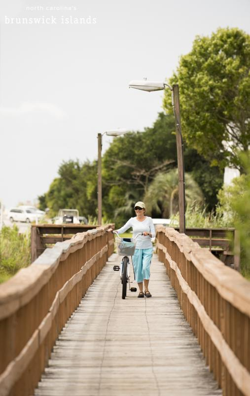 A woman walking her bike over a bridge in the Brunswick Islands, NC