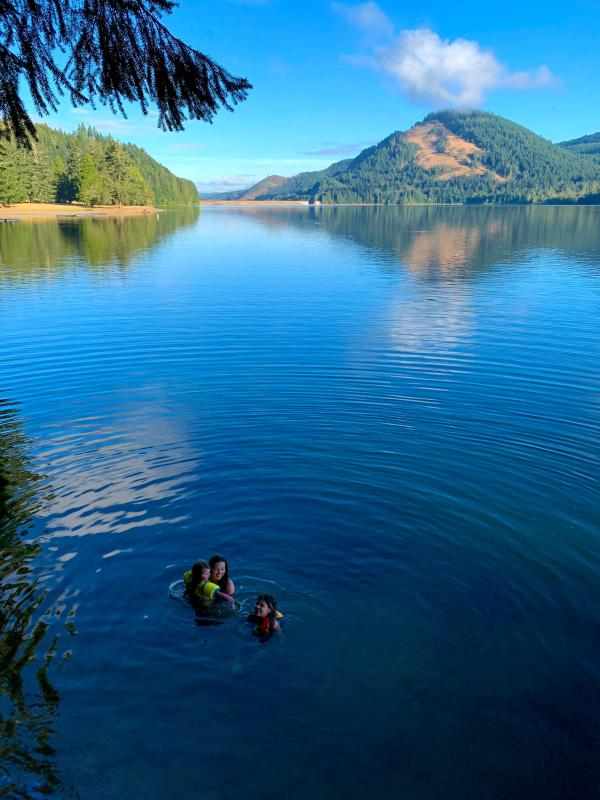 A woman and two young girls swim together in the deep blue waters at Dorena Lake which is surrounded by mountains.