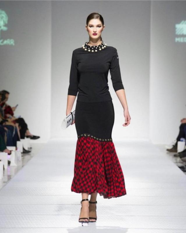 A model in a black and red dress walks down the runway at StyleWeek Northeast in Providence, Rhode Island