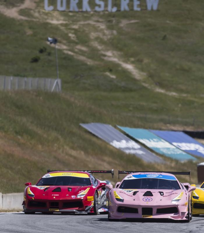 Cars racing at WeatherTech Raceway Laguna Seca with the Corkscrew sign in the background