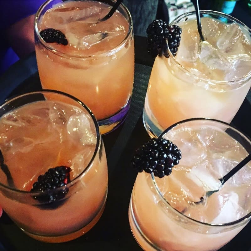 four bourbon glasses holding fruity bourbon cocktails and blackberries at the purple poulet bourbon bistro