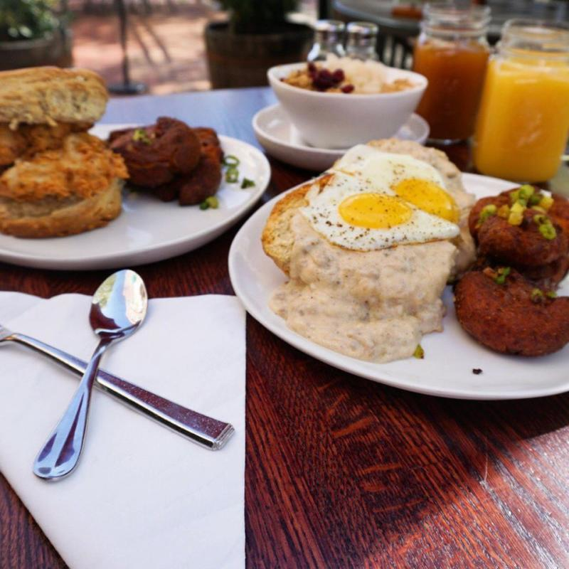 Plated dishes with a biscuit sandwich and biscuits and gravy from Hometown Harvest Brunch