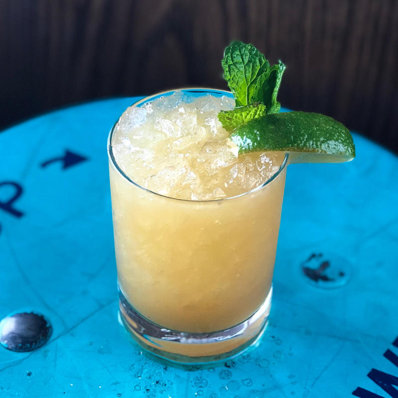 Mai Tai cocktail with mint leaves and lime on a blue tabletop