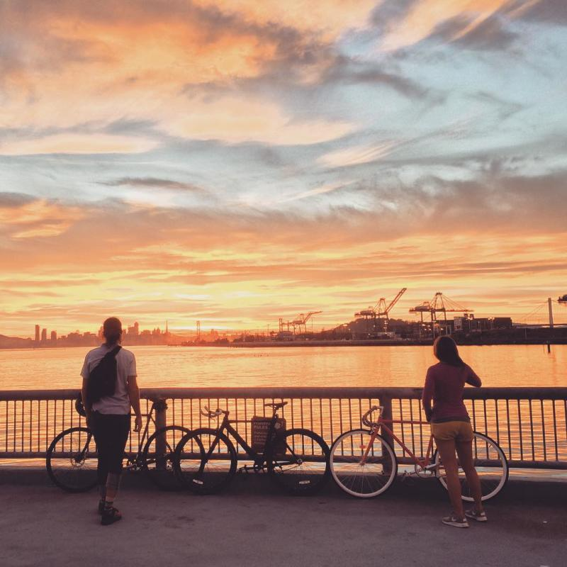 Man and woman with bicycles at Middle Harbor Shoreline Park at sunset