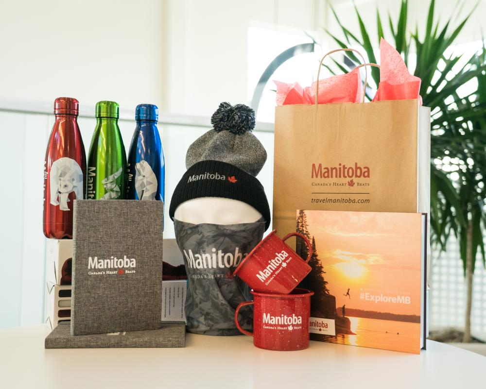 Travel Manitoba Merchandise including notebook, toque, water bottle, photo book, mugs, and more