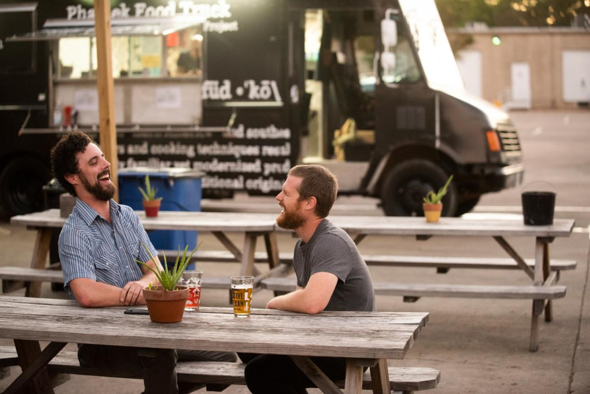 Local musician Doctor JOE and bandmate laugh while drinking beer at food truck in austin texas