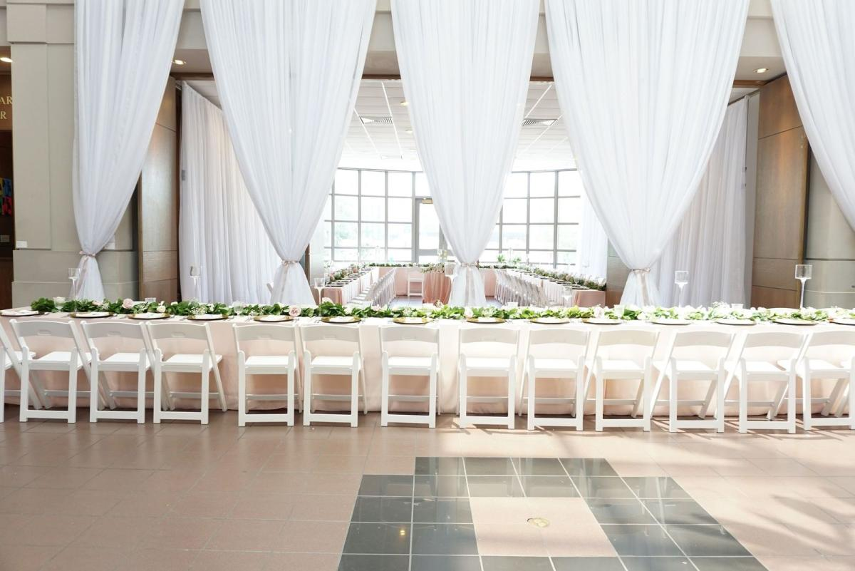 Large Row Of Dining Tables With White Plates And Table Cloths