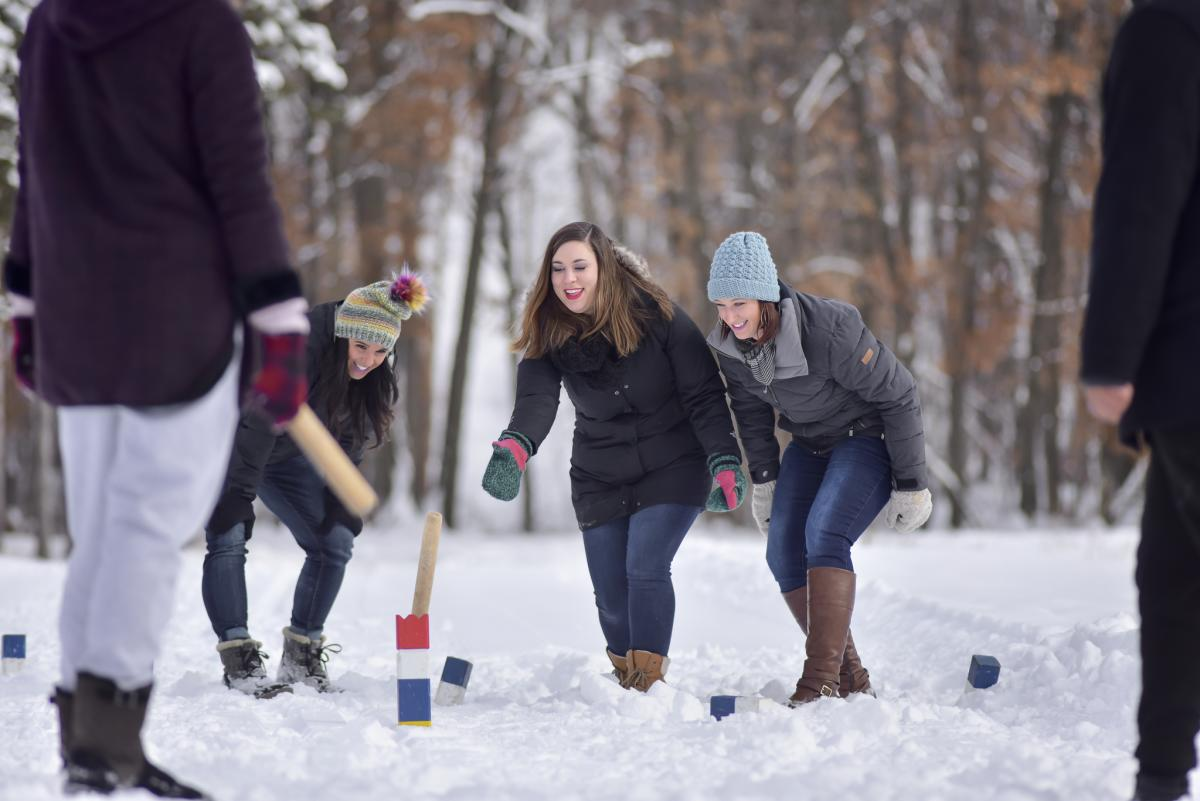 A group of people playing Kubb in the winter at Pinehurst Park