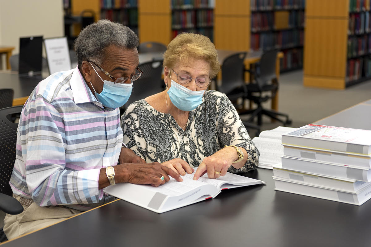 Two adults wearing masks looking through index books at the Genealogy Center in Fort Wayne, Indiana
