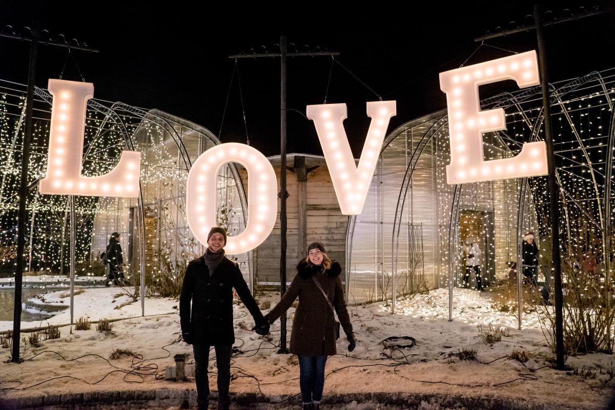 A couple stands in front of a lights display at the Zoo Lights Festival
