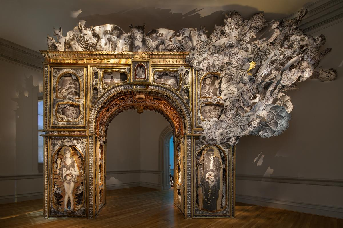 A freestanding arch that looks like the Arch de Triomphe from Burning Man made of Paper