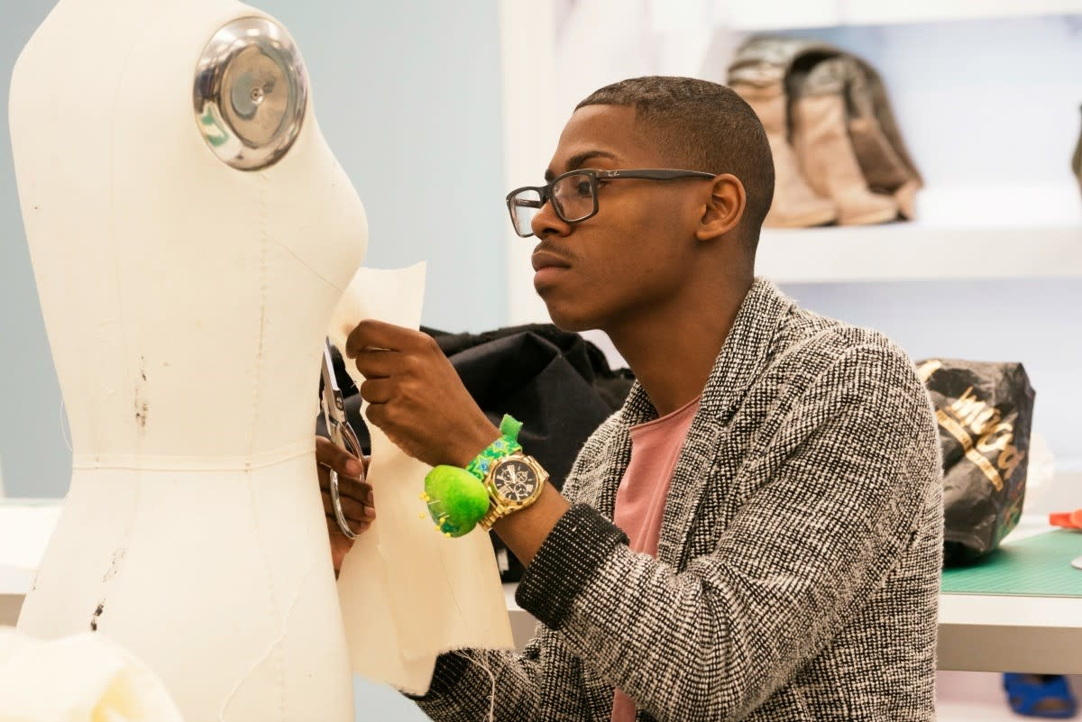 Fashion designer Cornelius Ortiz cuts fabric on a bust for StyleWeek Northeast in Providence, Rhode Island