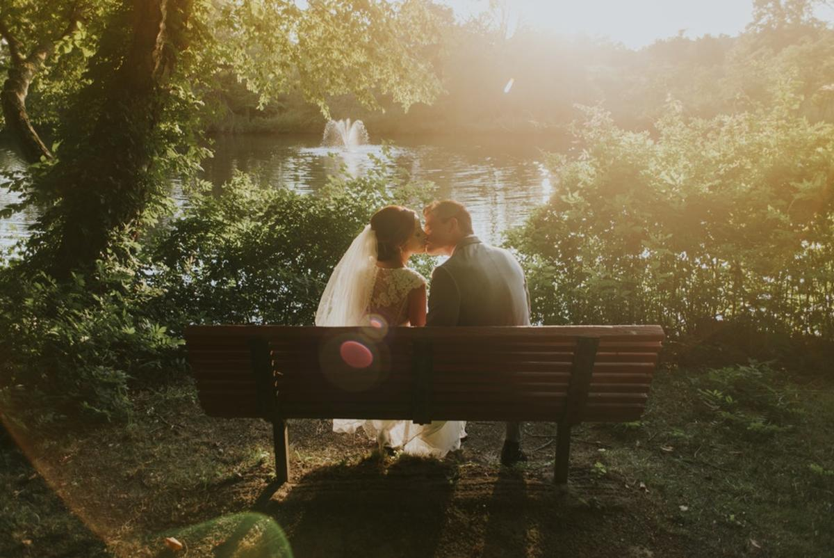 newlywed sitting on bench white kissing