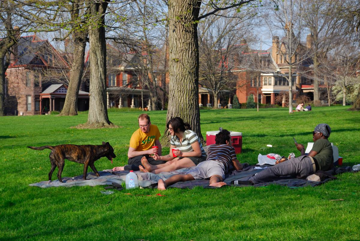 A group of four friends (and a dog) enjoys a picnic in Goodale Park