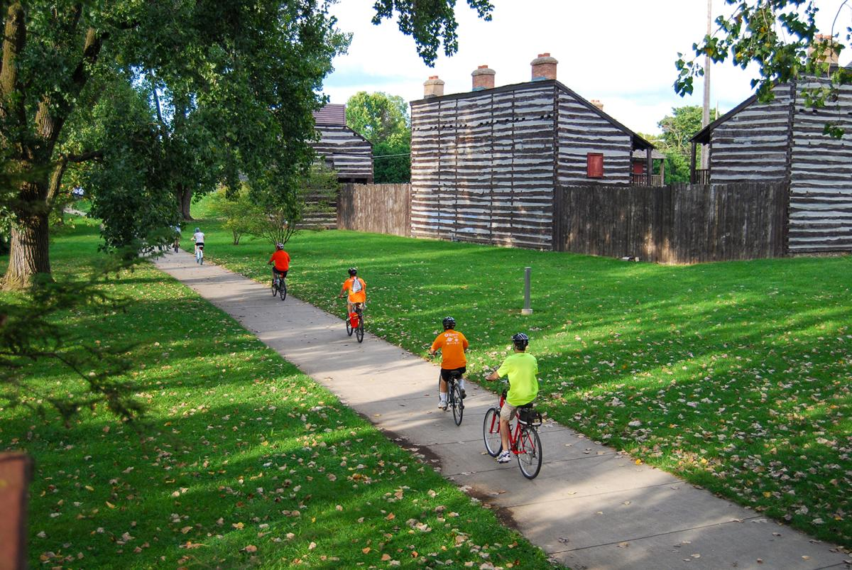 Family biking along Fort Wayne's downtown trails near the Old Fort