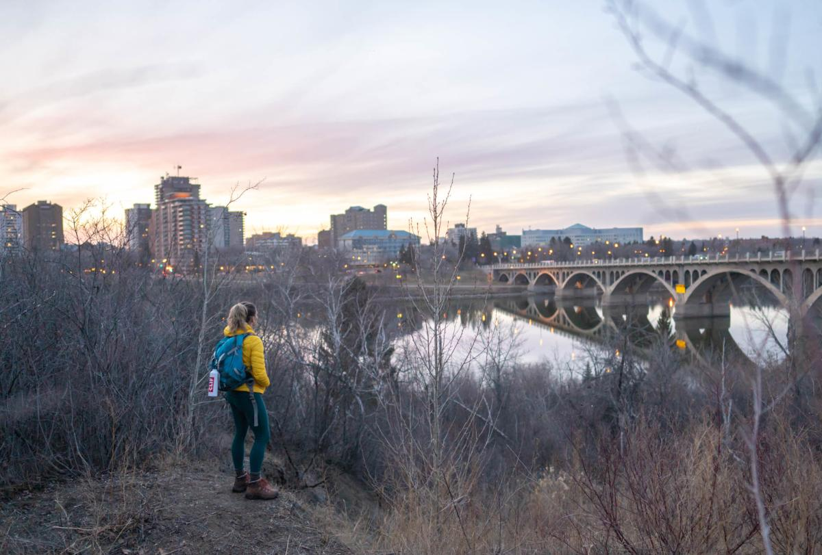 A hiker looks at the Saskatoon, SK skyline at sunset