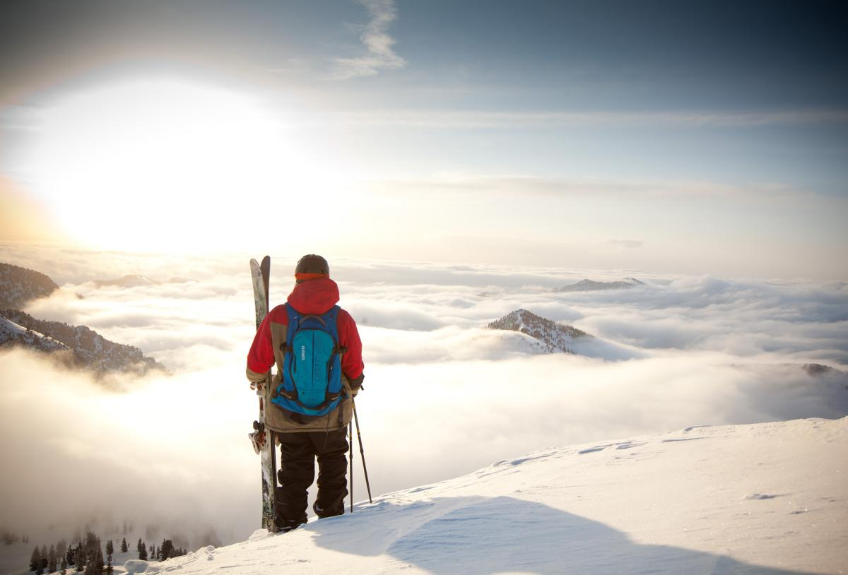 A skier, with skis in hand, standing on a mountain looking at the cloud filled valley below at a ski resort near Salt Lake City.