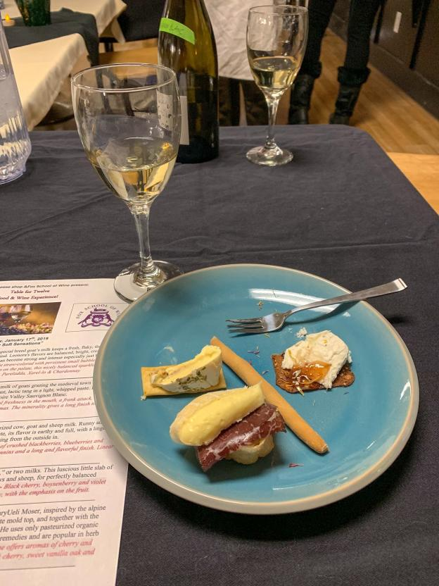 Wine glass and cheese pairing plate at the Table for Twelve