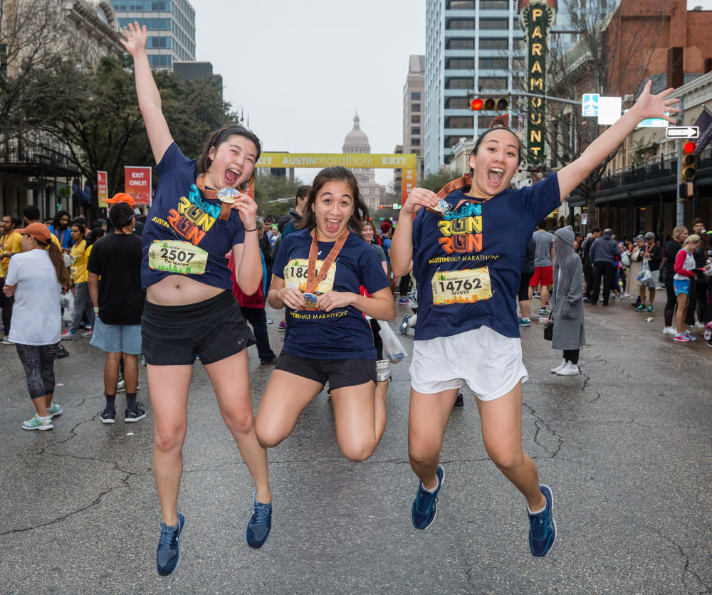 women jumping with medals at austin marathon finish line in austin texas
