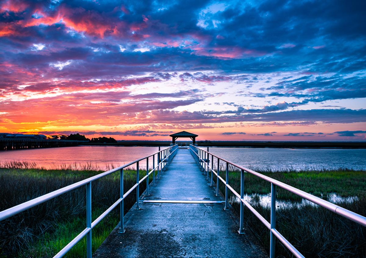A sunset paints the sky over the quiet marshes at Gascoigne Bluff Pier