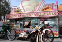 Custom motorcycle stretched out in front of a colorful hamburger stand.