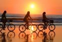 Three women enjoy a sunrise bicycle ride on Daytona Beach.