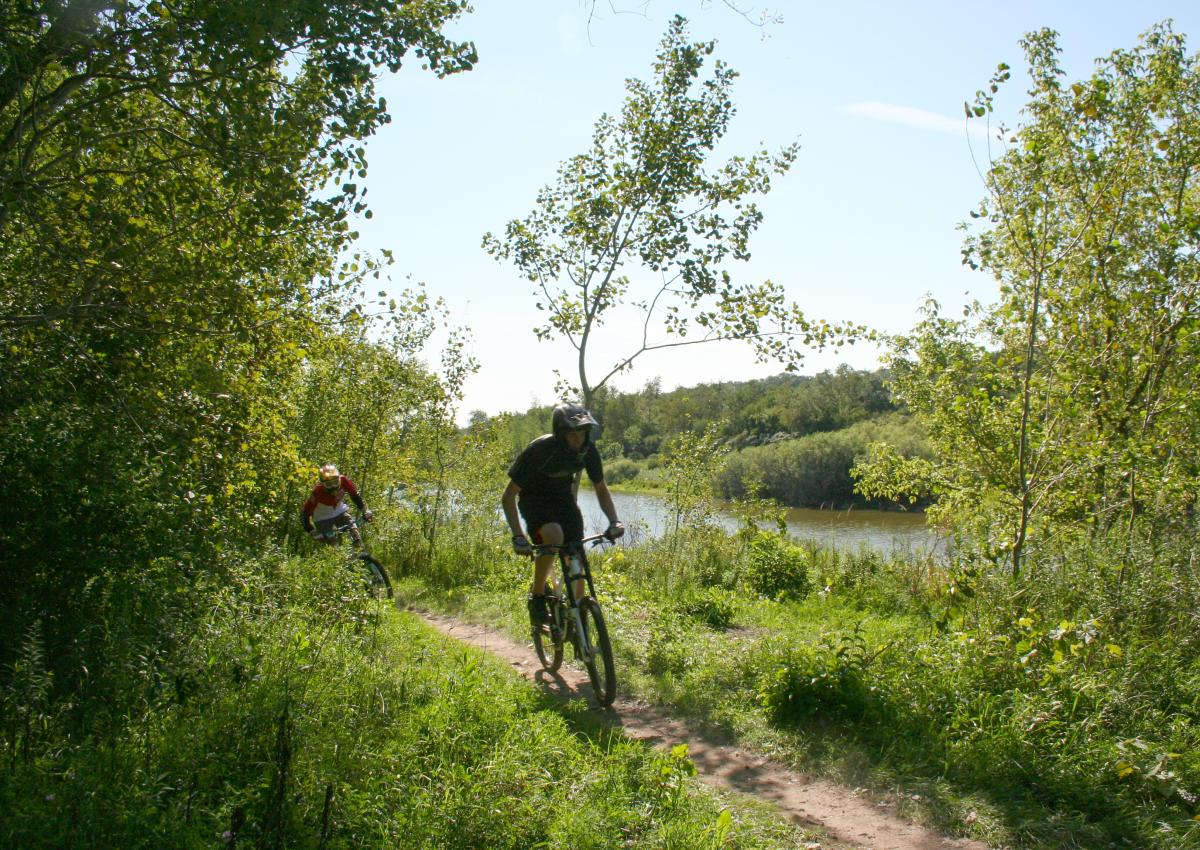 Two mountain bikers travel down a wooded path, next to a river