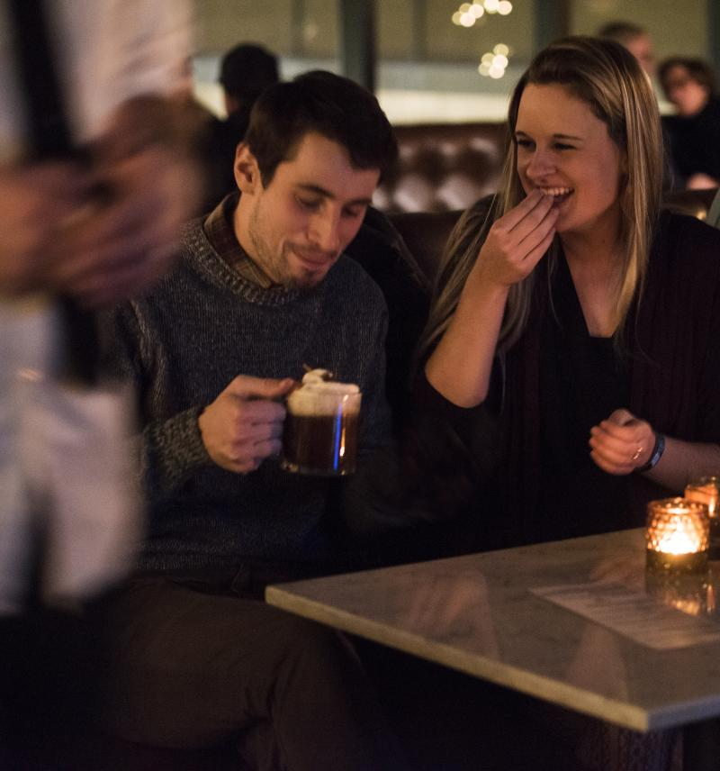 A couple enjoys a beer and night out at Dive, a bar in Eau Claire.