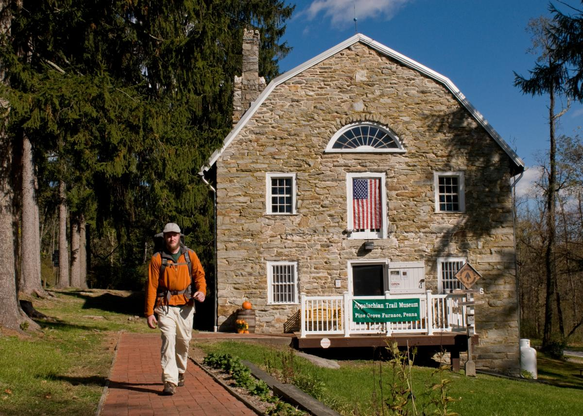 A hiker walks past the Appalachian Trail Museum, located along the A.T.