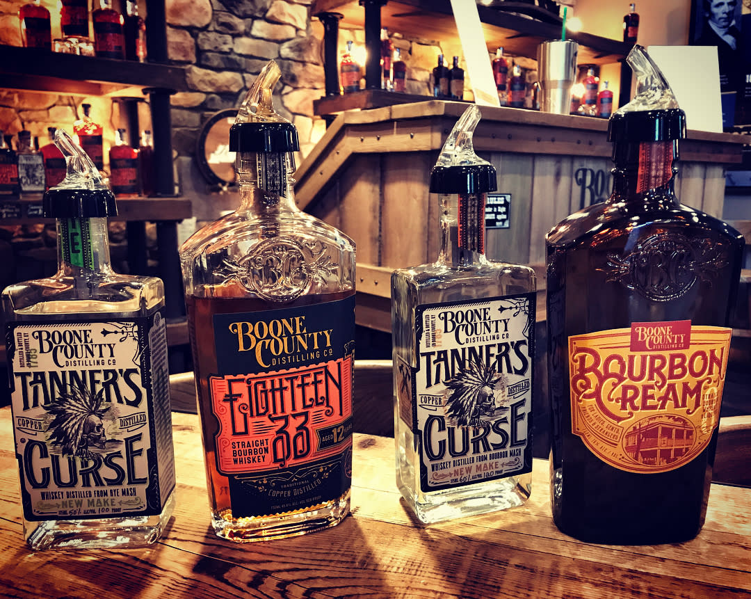 Two bottles of new make bourbon called Tanner's Curse, a brown bottle of Bourbon Cream and a bottle of 1833 bourbon on a wood table at Boone County Distilling Co.
