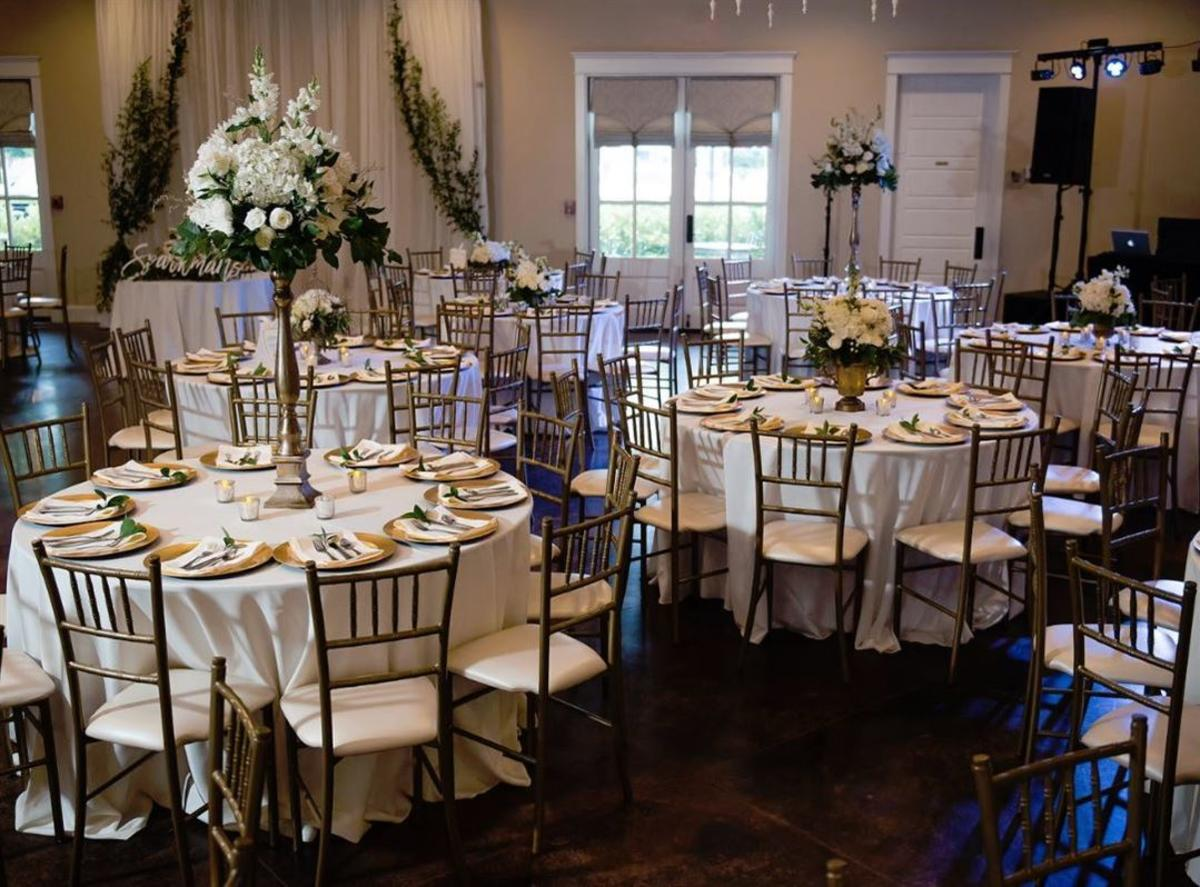 The Laurels Meeting Area With Flower Arrangement And Round Tables