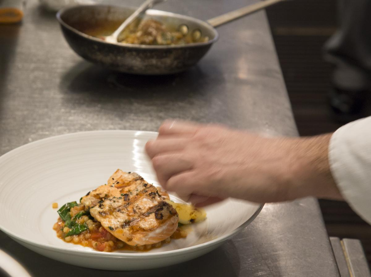 Chef adds finishing touches to Biba Restaurant Dine Downtown 2017 dish: Salmone con Frecola e Pomodoro - Grilled salmon on a bed of fregola stewed in fennel and tomatoes. Taken 1/3/2017