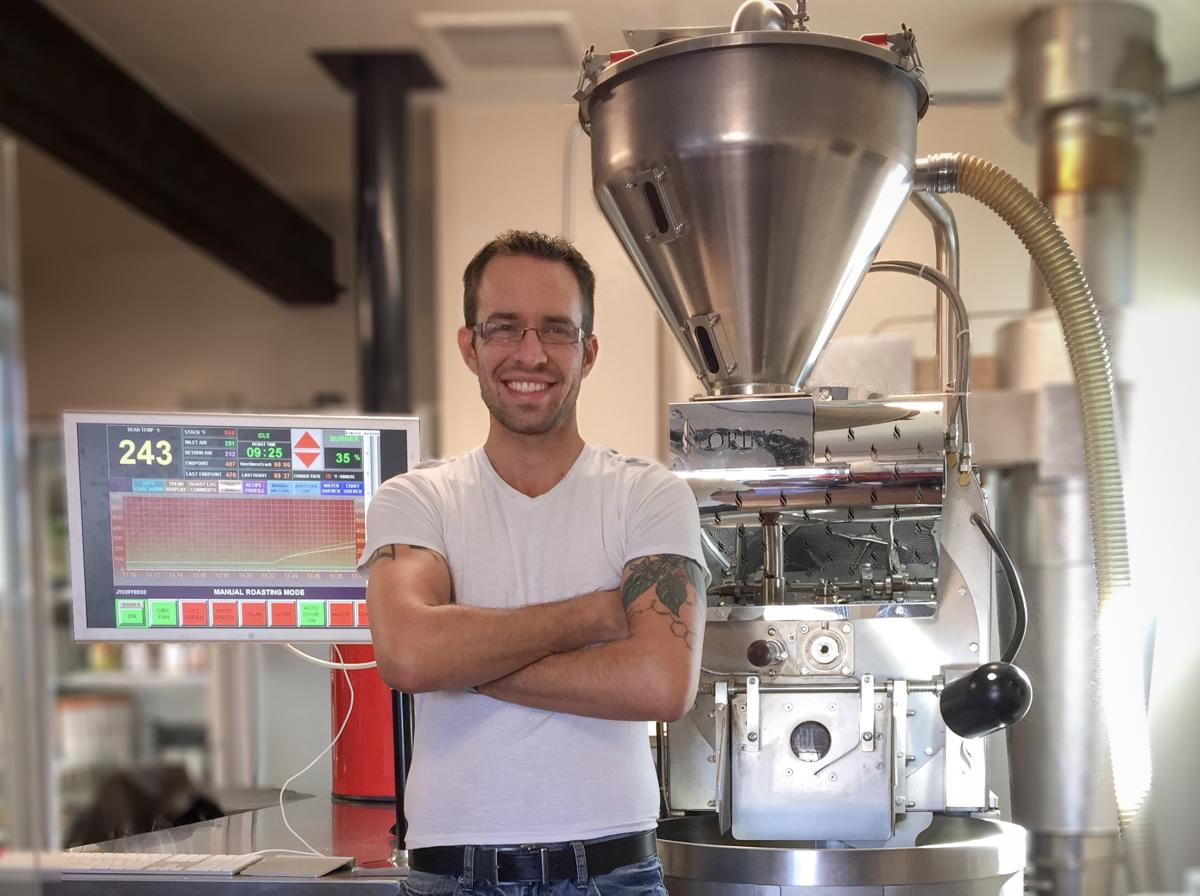 Joshua Tree Coffee Company owner Royce Robertson stands in front of a Loring S15 Falcon Smart Roaster.