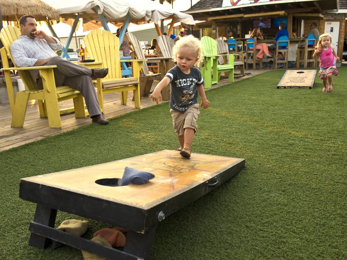 Toddler playing corn hole