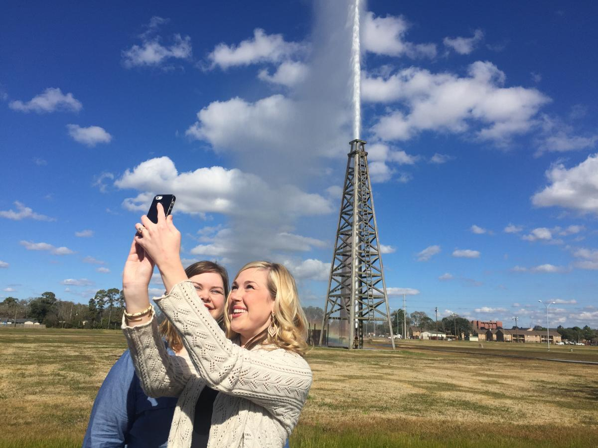 Visitors take a selfie at Spindletop as the gusher blows