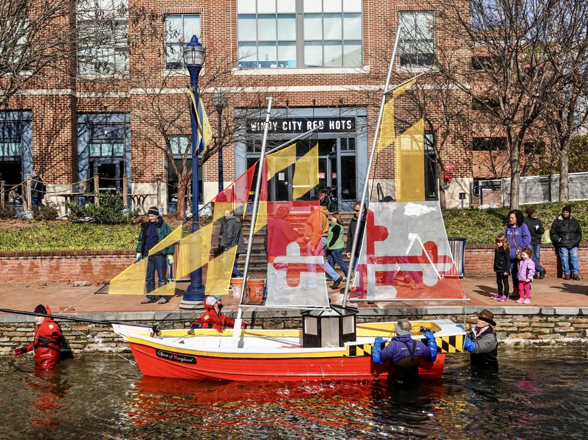 Yellow and red sailboat floating on Carroll Creek