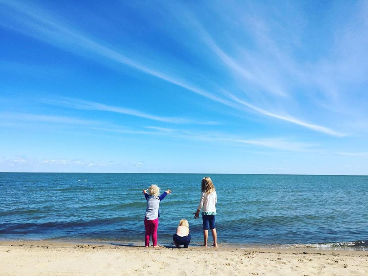 Kids looking out at the water from the sandy beach at Bay City State Park
