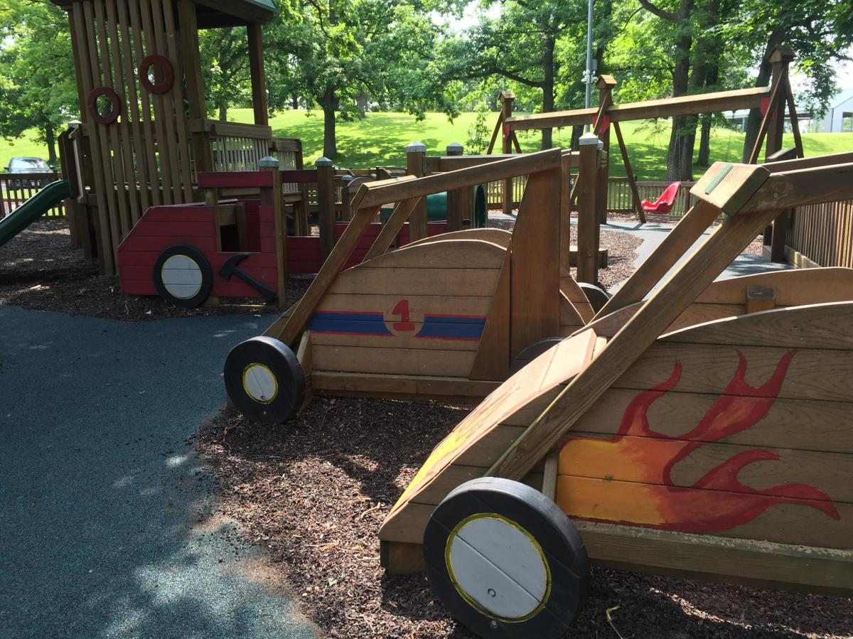 Three wooden, painted race cars for children to sit in. The closest car has flames on it. The second car as the number one on it and the third car has an ax on it.