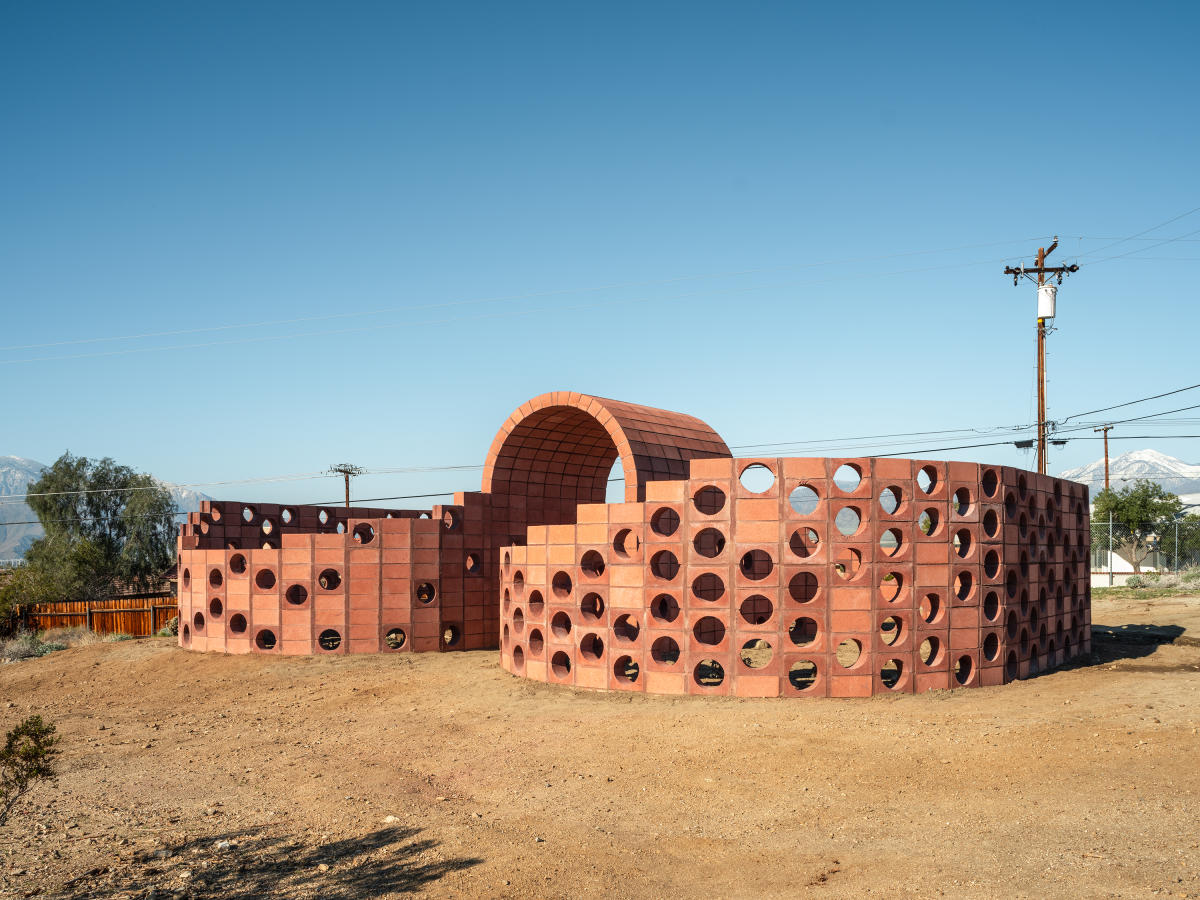 A brick-colored art installation in the desert