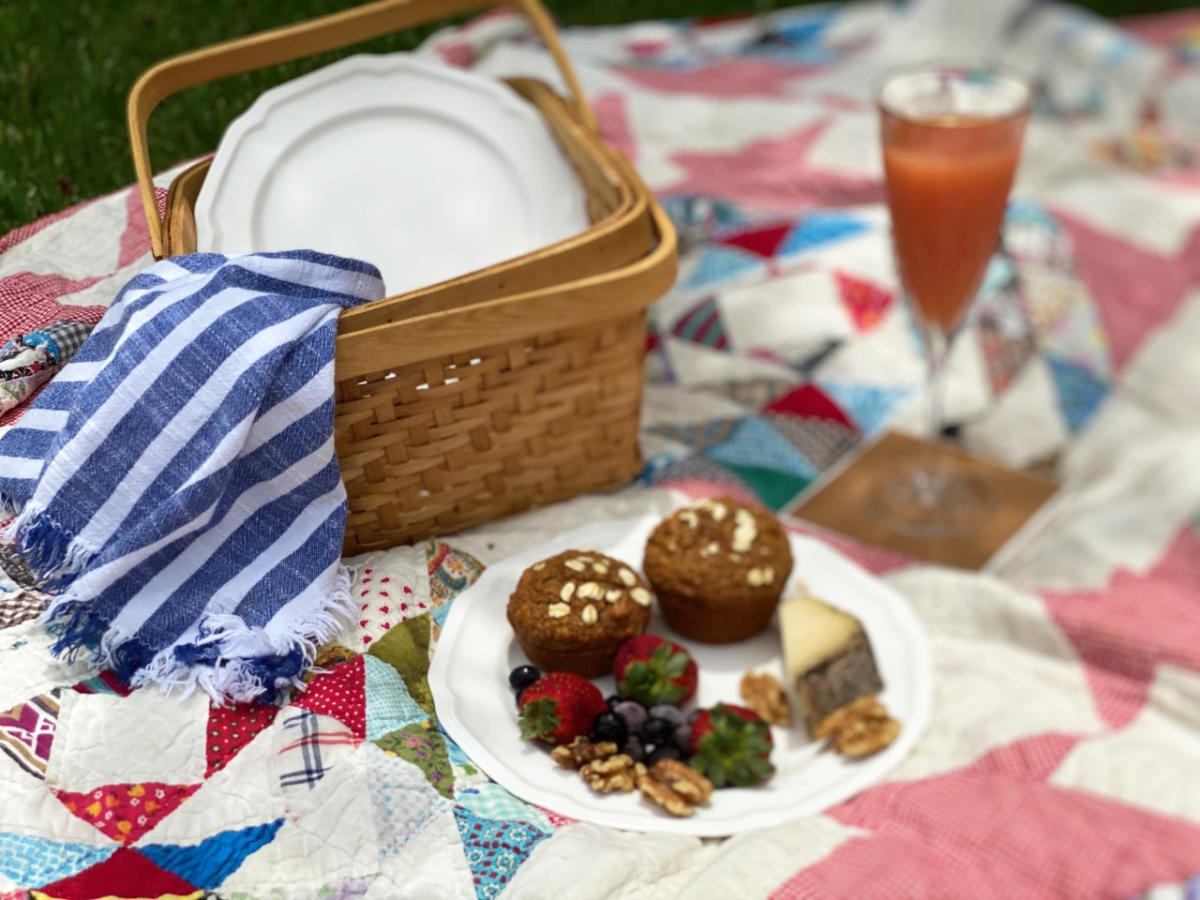 A picnic basket with muffins sits atop a hand-made quilt.