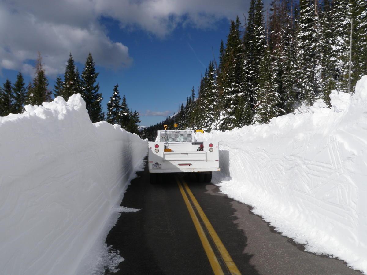 Truck dwarfed by snowbanks on trail ridge road
