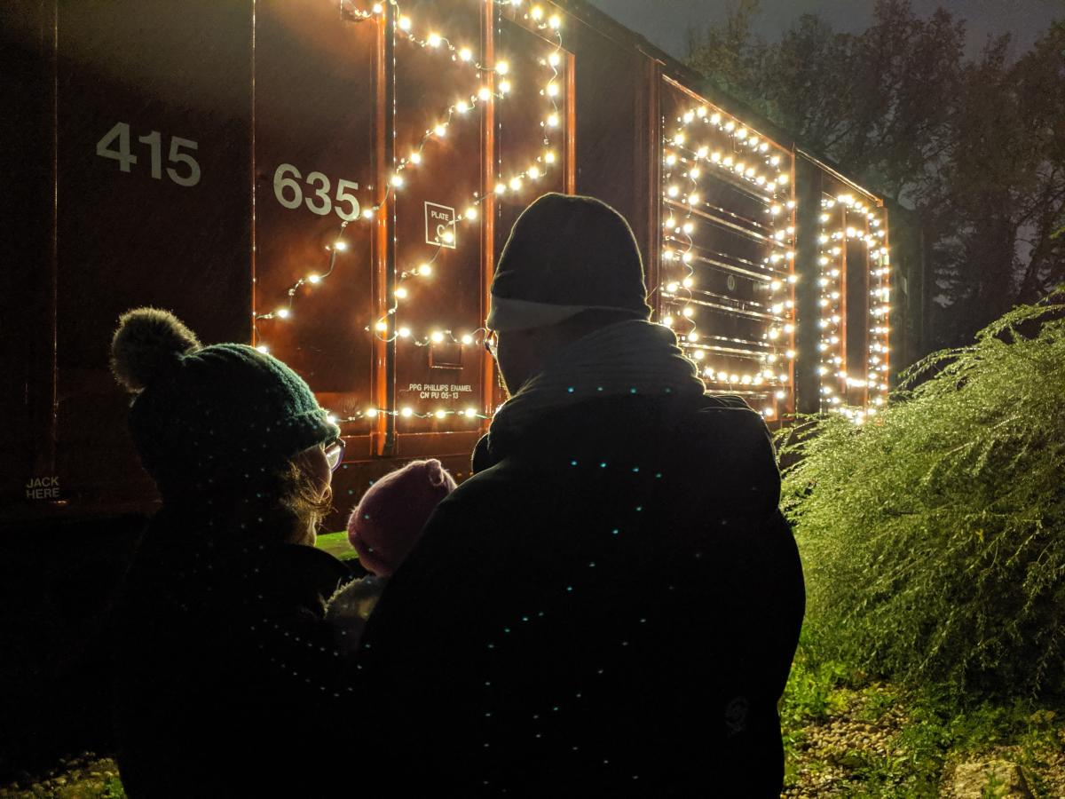 A family stands in front of a train car at the Zoo Lights Festival