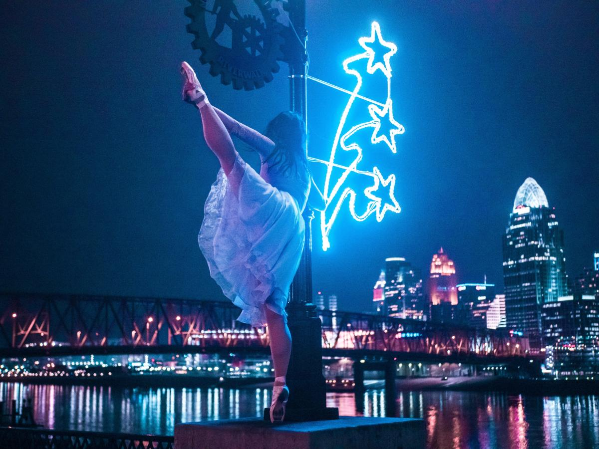A ballerina in white dancing on Newport on the Levee with the Cincinnati skyline and Ohio river in the background